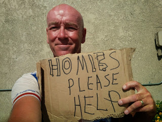 Geoff holding a sign reading 'Homies please help' during the cycling trip through America.