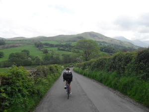 Cyclist riding through green English countryside during a coast to coast holiday